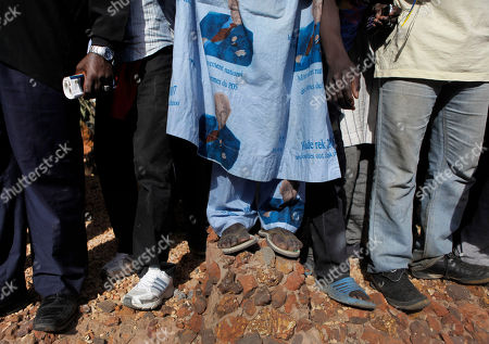A man wears an outfit made from cloth showing former President Abdoulaye Wade, with text saying that the women's movement of the Senegalese Democratic Party (PDS) supports him, as more than a thousand people rallied to call for the release of the former president's son, Karim Wade, who was arrested last week on corruption charges in Dakar, Senegal, . Authorities charged Karim Wade, the son of Senegal's former president Abdoulaye Wade, with illicit enrichment Wednesday, April 17, following a months-long investigation into how he allegedly amassed a fortune of more than US dlrs 1.3 billion