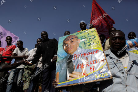 An opposition party militant holds up a poster of Karim Wade, as more than a thousand people rallied to call for the release of the former president's son, who was arrested last week on corruption charges in Dakar, Senegal, . In addition to calling for his liberation from prison, the poster reads 'Future President.' Authorities charged Karim Wade, the son of Senegal's former president Abdoulaye Wade with illicit enrichment Wednesday, April 17, following a months-long investigation into how he allegedly amassed a fortune of more than US dlrs 1.3 billion