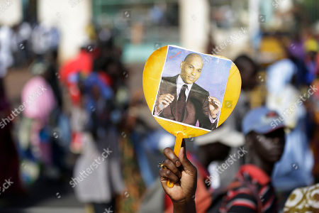 An opposition party militant holds up a heart-shaped fan bearing a picture of Karim Wade, as more than a thousand people rallied to call for the release of the former president's son, who was arrested last week on corruption charges in Dakar, Senegal, . Authorities charged the son of Senegal's former president Abdoulaye Wade with illicit enrichment Wednesday, April 17, following a months-long investigation into how he allegedly amassed a fortune of more than US dlrs1.3 billion