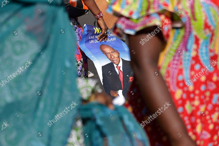 Stock Photo of A poster of former President Abdoulaye Wade is seen amidst women marching, as more than a thousand people rallied to call for the release of the former president's son, Karim Wade, who was arrested last week on corruption charges in Dakar, Senegal, . Authorities charged the son of Senegal's former president with illicit enrichment Wednesday, April 17, following a months-long investigation into how he amassed a fortune of more than $1.3 billion
