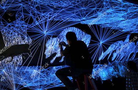 "Artists install an installation art piece seen under Ultra-violet lighting titled ""Stellar Cave II"" by French artist Julien Salaud on in Singapore which will host the Art Garden 2013 art festival for about 3-months at the Singapore Art Museum"