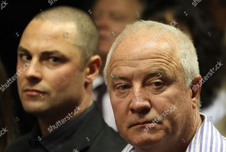 Olympic athlete Oscar Pistorius' father Henke Pistorius, right, with his son Carl watch as Oscar Pistorius walks in during his bail hearing at the magistrate court in Pretoria, South Africa
