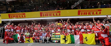 Ferrari driver Fernando Alonso of Spain, center, flanked by his father Jose Luis and his mother Ana Diaz, celebrates in the Ferrari pit after the Formula One Spanish Grand Prix, at the Catalunya racetrack in Montmelo, near Barcelona, Spain, . At left is Ferrari team principal Stefano Domenicali and third place Ferrari driver Felipe Massa of Brazil. Alonso won the race