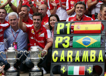 Ferrari driver Fernando Alonso of Spain, center, flanked by his father Jose Luis and his mother Ana Diaz, celebrates in the Ferrari pit after the Formula One Spanish Grand Prix, at the Catalunya racetrack in Montmelo, near Barcelona, Spain, . Alonso won the race