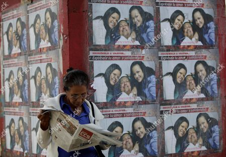 "A woman reads a newspaper next to a wall covered with posters showing Venezuela's President Hugo Chavez pictured with his daughters Maria Gabriela, and Rosa Virginia, outside the military hospital in Caracas, Venezuela, . A brief statement read on national television by Communications Minister Ernesto Villegas late Monday carried the sobering news about the charismatic 58-year-old leader's deteriorating health. Villegas said Chavez is suffering from ""a new, severe infection."" The state news agency identified it as respiratory"