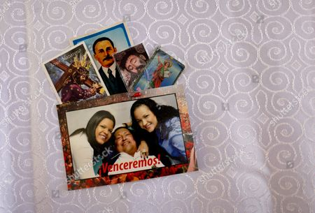 "A postcard of Venezuela's President Hugo Chavez with his daughters; Maria Gabriela, left, and Rosa Virginia, is pinned together with prayer cards to the altar cloth in the military hospital's chapel, in Caracas, Venezuela, . A brief statement read on national television by Communications Minister Ernesto Villegas late Monday carried the sobering news about the charismatic 58-year-old leader's deteriorating health. Villegas said Chavez is suffering from ""a new, severe infection."" The state news agency identified it as respiratory"
