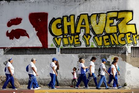 "Pedestrians walks past graffiti that reads in Spanish; ""Chavez lives and will prevail,"" outside the military hospital in Caracas, Venezuela, . A brief statement read on national television by Communications Minister Ernesto Villegas late Monday carried the sobering news about the charismatic 58-year-old leader's deteriorating health. Villegas said President Hugo Chavez is suffering from ""a new, severe infection."" The state news agency identified it as respiratory"