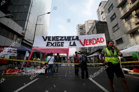 "Student protestors demanding more information about President Hugo Chavez's health, sleep under a banner that reads in Spanish; ""Venezuela demands the truth,"" in Caracas, Venezuela, . A brief statement read on national television by Communications Minister Ernesto Villegas late Monday carried the sobering news about the charismatic 58-year-old leader's deteriorating health. Villegas said Chavez is suffering from ""a new, severe infection."" The state news agency identified it as respiratory"