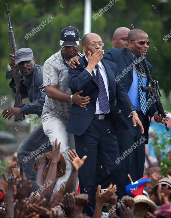 Stock Photo of Jean Bertrand Aristide Former Haitian President Jean-Bertrand Aristide, flanked by body guards,greets supporters as he leaves the courthouse in Port-au-Prince, Haiti. Aristide greeted a small group of onlookers after testifying before a judge investigating the slaying of one of the country's most prominent journalists. The judge is questioning Aristide about the 2000 killing of Jean Dominique, a friend of the former president
