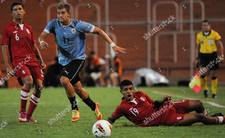 Gianni Rodriguez, Wilder Cartagena Uruguay's Gianni Rodriguez, center, vies for the ball with Peru's Wilder Cartagena, right, during an U-20 South American soccer championship match in Mendoza, Argentina