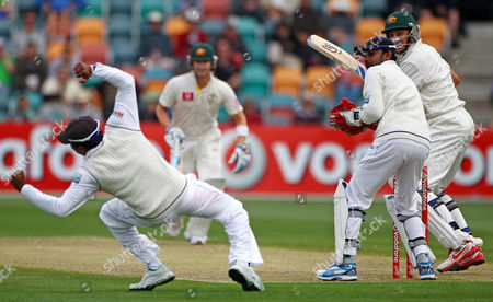 Sri Lanka's Prasanna Jayawardene, second right, turns to see his captain Mahela Jayawardene, left, dive in a fielding attempt off Australia's Mike Hussey, ryght, on the first day of their cricket test match at Bellerive Oval in Hobart