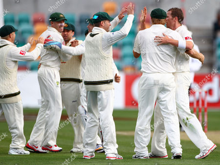 Australia's Peter Siddle, right, and Mike Hussey, second left, celebrate after they combined to take the wicket of Sri Lanka's Kumar Sangakkara for 4 runs on the second day of their cricket test match at Bellerive Oval in Hobart, . Australia declared at 450-5 in their first innings