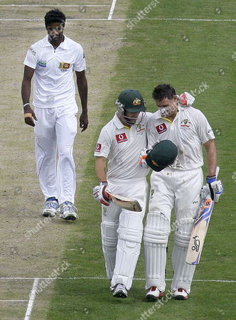 Australia's Mike Hussey, right, is congratulated by teammate Matthew Wade after Hussey 100 runs as Sri Lanka's Shaminda Eranga walks behind on the second day of their cricket test match at Bellerive Oval in Hobart