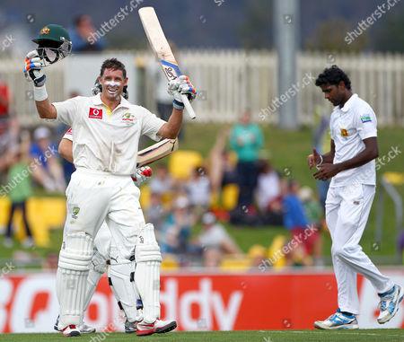 Mike Hussey, Shaminda Eranga Australia's Mike Hussey, left, celebrates after making 100 runs as Sri Lanka's Shaminda Eranga, right, looks down on the second day of their cricket test match at Bellerive Oval in Hobart, Australia
