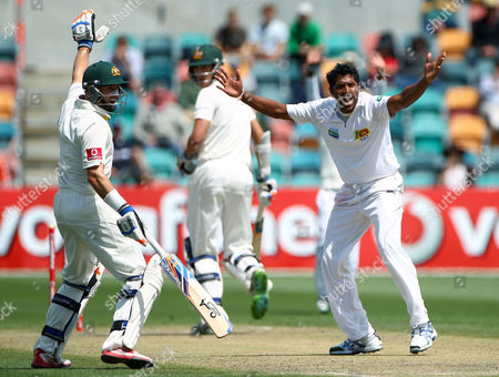 Sri Lanka's Chanaka Welegedara, right, appeals for, and is granted, a LBW decision on Australia's Mitchell Starc, center, as Mike Hussey, left, signals his batting partner on the fourth day of their cricket test match at Bellerive Oval in Hobart, Australia, . Sri Lanka need 393 in their second innings to win