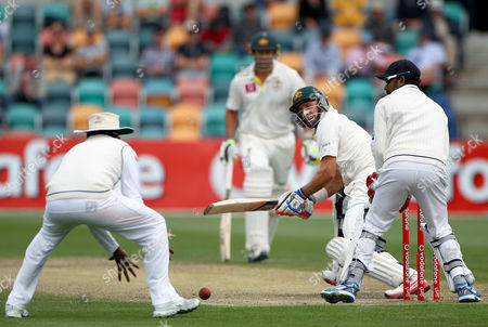 Australia's Mike Hussey, second from right, plays a reverse sweep to Sri Lanka's Mahela Jayawardene, left, on the fourth day of their cricket test match at Bellerive Oval in Hobart, Australia, . Sri Lanka need 393 in their second innings to win