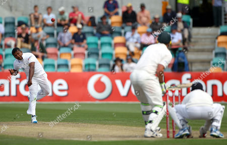 Sri Lanka's Rangana Herath, left, bowls to Australia's Mike Hussey, center, on the fourth day of their cricket test match at Bellerive Oval in Hobart, Australia, . Sri Lanka need 393 in their second innings to win