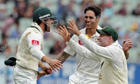 Australia's players Ed Cowen, left, Mitchell Johnson, center, and Mike Hussey celebrate the wicket of Tillakaratne Dilshan caught by Cowan off the bowling of Johnson during their cricket test match at the Melbourne Cricket Ground, Australia