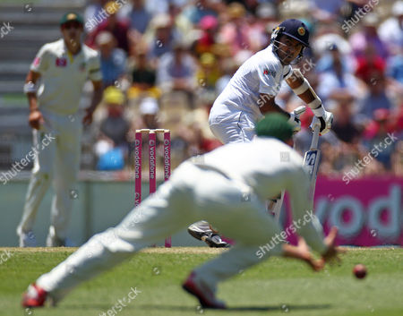 Sri Lanka's Mahela Jayawardene, back, turns to see an edge not carry to Australia's Mike Hussey on the first day of their cricket test match in Sydney, Australia