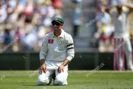 Australia's Mike Hussey kneels on the ground after a field ing chance against Sri Lanka during their cricket test match in Sydney, Australia