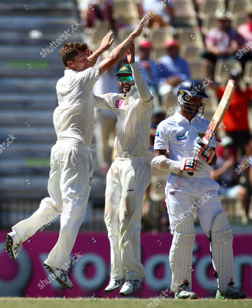 Australia's Jackson Bird, left, and Ed Cowan celebrate after Sri Lanka's Dimuth Karunaratne, right, was caught behind for 85 runs on the third day of their cricket test match in Sydney, Australia, . Australia are declared 432 for 9 in reply to Sri Lanka's 294 all out in their first innings