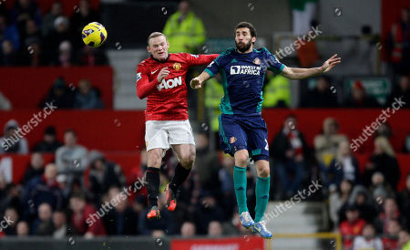 Manchester United's Wayne Rooney, left, fights for the ball with Sunderland's Carlos Cuellar during their English Premier League soccer match at Old Trafford Stadium, Manchester, England