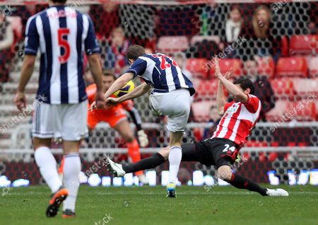 West Bromwich Albion's Zoltan Gera, center, scores his goal past Sunderland's Carlos Cuellar, right, during their English Premier League soccer match at the Stadium of Light, Sunderland, England