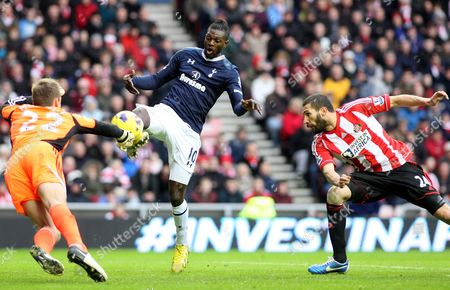 Tottenham Hotspurs' Emmanuel Adebayor, center, has a shot toward's goal past Sunderland's goalkeeper Simon Mignolet, left, and Carlos Cuellar, right, during their English Premier League soccer match at the Stadium of Light, Sunderland, England