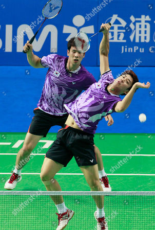 Stock Photo of Ko Sung-hyun, Lee Yong-dae South Korea's Ko Sung-hyun, left, and Lee Yong-dae play against China's Cai Yun Cai and Fu Haifeng during their men's doubles quarterfinal match of the China Open World Superseries Premier badminton competition in Shanghai, China on . Ko and Lee won 21-17, 21-16