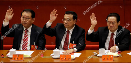 Li Keqiang, Li Changchun, Zhou Yongkang Chinese Vice Premier Li Keqiang, center, Propaganda chief Li Changchun, left, and a head of Political and Legislative Affairs Committee Zhou Yongkang raise their hands to show approval for a work report during the closing ceremony for the 18th Communist Party Congress at the Great Hall of the People in Beijing, China