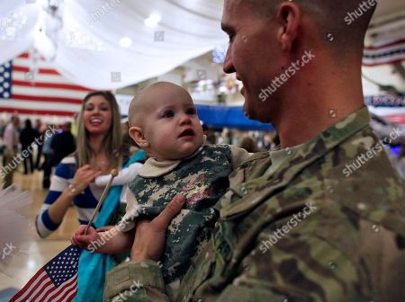 Sgt. Andrew Baldwin holds his baby Elauna during a homecoming ceremony for soldiers returning from a deployment in Afghanistan, at Fort Carson, Colo., . A group of soldiers from the 4th Brigade Combat Team, 4th Infantry Division, arrived Wednesday after finishing their tour