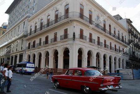 Stock Picture of An American classic car drives by the building where Sloppy Joe's bar is in Havana, Cuba, . Sloppy Joe's will be reopened in February 2013 by the state-owned tourism company Habaguanex, part of an ambitious revitalization project by the Havana City Historian's Office, which since the 1990's has transformed block after block of crumbling ruins into rehabilitated buildings along vibrant cobblestone streets, giving residents and tourists from all over the chance to belly up to the same bar that served thirsty celebrities like Rock Hudson, Babe Ruth and Ernest Hemingway