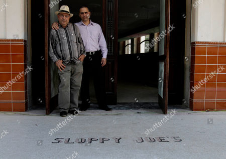 Jose Rafa Malem, 59, left, and Ernesto Iznaga pose for a photo in the entrance of Sloppy Joe's Bar in Havana, Cuba, . Sloppy Joe's will be reopened in February 2013 by the state-owned tourism company Habaguanex, part of an ambitious revitalization project by the Havana City Historian's Office, which since the 1990's has transformed block after block of crumbling ruins into rehabilitated buildings along vibrant cobblestone streets, giving residents and tourists from all over the chance to belly up to the same bar that served thirsty celebrities like Rock Hudson, Babe Ruth and Ernest Hemingway