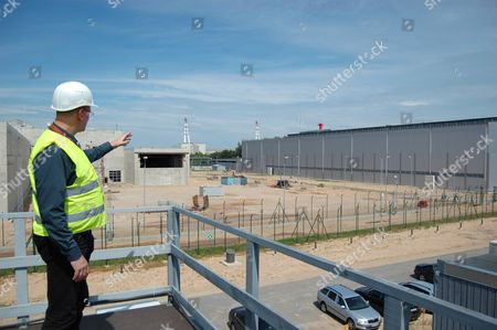 In this July 2012 photo, Thomas Pietsch, site manager for Nukem Technologies, a firm contracted for decommissioning projects for Lithuania's Soviet-era nuclear power plant, points to the unfinished nuclear fuel storage facility near the nuclear power plant in Ignalina, Lithuania. Three years after the nuclear plant was shut down due to safety concerns, there is still nuclear fuel inside one of the two reactors. The temporary storage facilities for spent fuel and radioactive waste are four years behind schedule. The problems have prompted threats from the European Union to sever funding and raising concerns that the facility will be around for years, possibly decades, longer than planned. The giant ventilation stacks in the background are part of the nuclear power plant