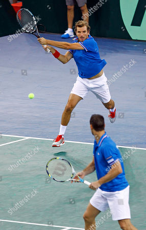 French player Julien Benetteau, top, returns the ball as Michael Llodra looks on during their doubles match against Israel pair Dudi Sela and Jonathan Erlich in the first round of the Davis Cup, in Rouen, western France, . Benetteau and Llodra won the match, and France qualifies for the next round on a 3-0 score