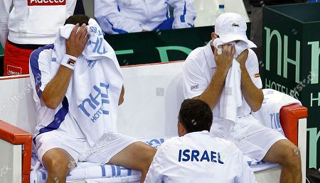 Israel players Dudi Sela, right, and Jonathan Erlich wipe their faces as they listen to the advice of team coach Eyal Ran during their doubles match against French pair Michael Llodra and Julien Benetteau in the first round of the Davis Cup between Israel and France, in Rouen, western France, . Llodra and Benetteau won the match, qualifying France for the next round on a 3-0 score
