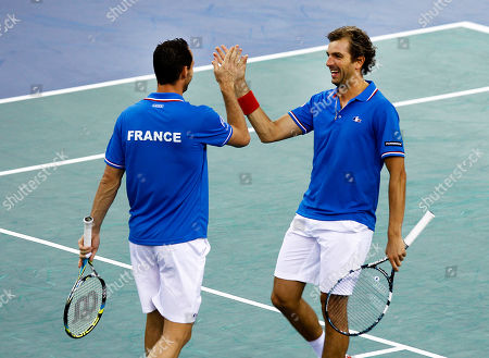 French player Michael Llodra, left, and Julien Benetteau, right, react after winning the double match against Israeli pair Dudi Sela and Jonathan Erlich, on the first round of the Davis Cup between Israel and France, in Rouen, western France, . France wins the first round on a 3-0 score