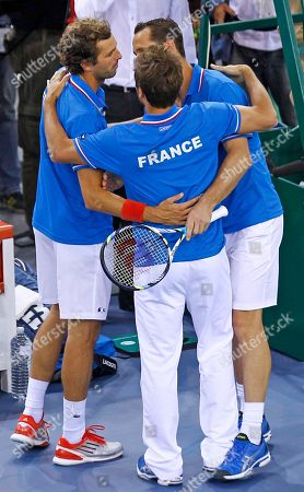 The French pair Michael Llodra, right, and Julien Benetteau, left, are congratulated by team captain Arnaud Clement, after they won the double match against Israeli pair Dudi Sela and Jonathan Erlich, on the first round of the Davis Cup between Israel and France, in Rouen, western France, . France wins the first round on a 3-0 score