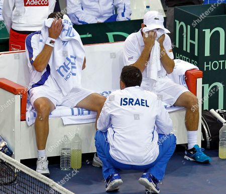 Israeli player Dudi Sela, right, and Jonathan Erlich, left, wipe their faces as they listen to the advice of team coach Eyal Ran, during their doubles match against French pair Michael Llodra and Julien Benetteau on the first round of the Davis Cup between Israel and France, in Rouen, western France, . Llodra and Benetteau won the match, qualifying France for the next round on a 3-0 score