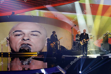 Stock Image of Dominique Ane French singer Dominique Ane, known as Dominique A, right, with his face projected on the screen, performs prior to receive the men's artist of the year award during the 28th Victoires de la Musique annual ceremony, France's top music awards, at the Zenith concert hall, in Paris, France