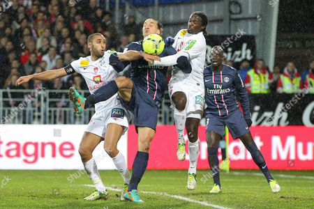 Stock Image of Swedish forward Zlatan Ibrahimovic of Paris Saint Germain, center, challenges for the ball with Brest's Ahmed Kantari, left, and Bernard Mendy, right, during their French League One soccer match, in Brest, western France