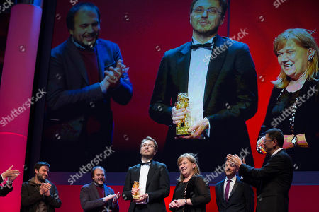 Calin Peter Netzer, Ada Solomon Director Calin Peter Netzer, centre left, holds the Golden Bear for his film Child's Pose alongside producer Ada Solomon, centre right, as Jury President Wong Kar Wai, right, applauds at the closing ceremony at the 63rd edition of the Berlinale, International Film Festival in Berlin