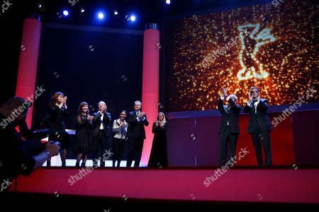 From left, jury members Susanne Bier, Athina Rachel Tsangari, Andreas Dresen, Shirin Neshat, Tim Robbins, Ellen Kuras, festival director Dieter Kosslick and jury president Wong Kar Wai applaud onstage during the opening ceremony at the 63rd edition of the Berlinale, International Film Festival in Berlin, Thursday, Feb.7,2013