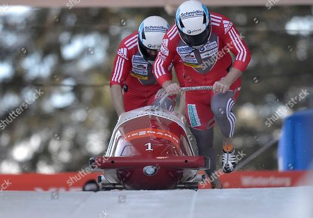 Beat Hefti, right, and Thomas Lamparter of Switzerland start during the 2 Man Bob World Cup race in Winterberg, Germany, . The Swiss double won the world cup in Winterberg
