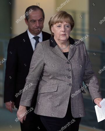 German Chancellor Angela Merkel, right, and the Prime Minister of Malta, Lawrence Gonzi, left, arrive for a joint press conference as part of a meeting at the chancellery in Berlin, Germany