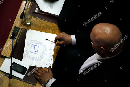 Lawmaker Ilias Panagiotaros, of the extreme right Golden Dawn party, sketches his party logo on a piece of paper during a debate in Parliament session in Athens early . The party sought an investigation of two former prime ministers over an emerging scandal involving the handling by authorities of data on Greeks with Swiss bank accounts. Lawmakers rejected the proposal but voted by an overwhelming majority to investigate former finance minister George Papaconstantinou _ a probe backed by all political parties in the 300-member assembly