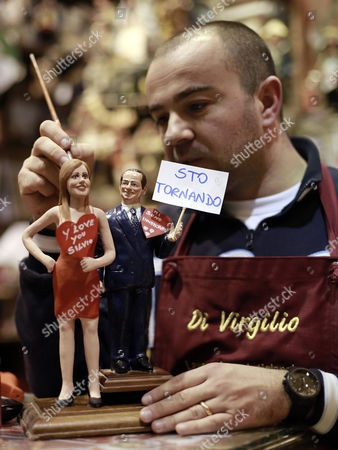 "Nativity scenes designer Genny Di Virgilio puts the final touches on two statuettes depicting former premier Silvo Berlusconi, right, holding a sign reading ""I'm coming back"" and a red heart reading ""I've fallen in love"", and his new girlfriend Francesca Pascale, in his shop in Naples, Italy, . In a weekend interview, Berlusconi apologized for the ""bunga bunga"" parties, saying he was lonely after having split of with his second wife, Veronica Lario who left him in 2008, citing alleged dalliances with young women. He also revealed he is engaged to a woman almost 50 years his junior, and says that ""finally I feel less alone."" The 76-year-old media baron said Sunday his engagement to 28-year-old Francesca Pascale - part of a support group called ""Silvio, we miss you"" - is ""official"