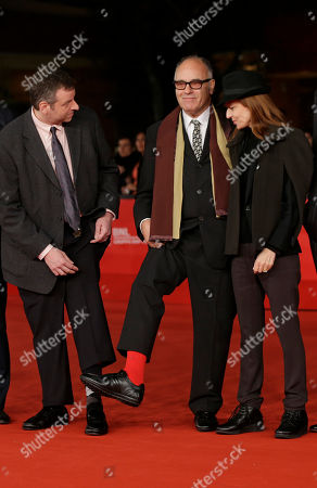 Director Amos Poe, center, shows his red sock as Brian Fass, left, and actress Loretta Mugnai looks at him as they arrive for the opening ceremony of the 7th edition of the Rome International Film Festival in Rome