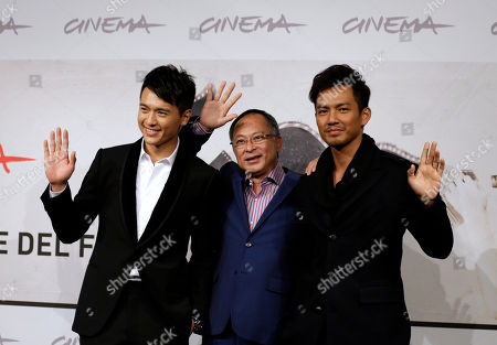 """Director Johnnie To, center, poses to present the movie """"Duzhan"""" flanked by actors Gao Yun Xiang, left, and Wallace Chung at the 7th edition of the Rome International Film Festival in Rome"""