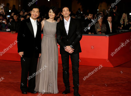 """From left, actor Zhang Guoli, actress Xu Fan, and actor Adrien Brody pose for photographers as they arrive for the screening of their movie """"1942"""" during the 7th edition of the Rome International Film Festival in Rome"""